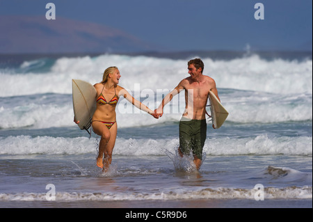 A couple having fun in the surf. - Stock Photo