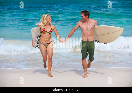 A couple of surfers enjoying a day at the beach - Stock Photo