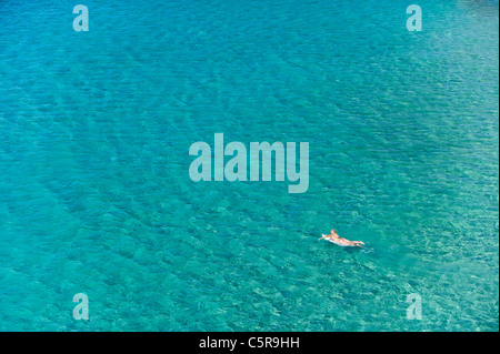 A surfer paddles her board out onto the Ocean. - Stock Photo