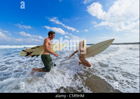 Two surfers run through the waves. - Stock Photo