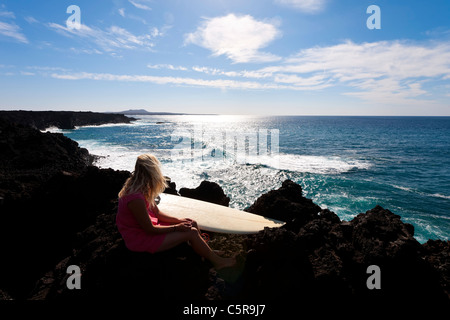 A surfer looks out over the Ocean. - Stock Photo