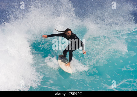 Surfer balanced riding beautiful blue wave.