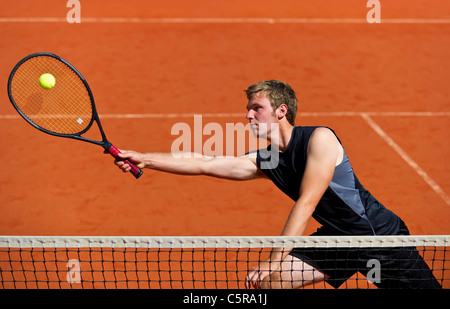 A tennis player at the net stretches to play ball. - Stock Photo