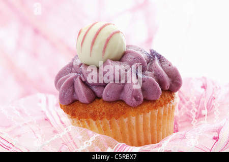 Close up of buttercream black currant cupcake with chocolate truffle - Stock Photo