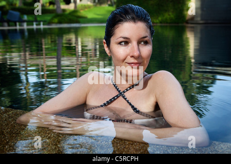 Portrait of a young woman in an outdoor pool in Asia - Stock Photo