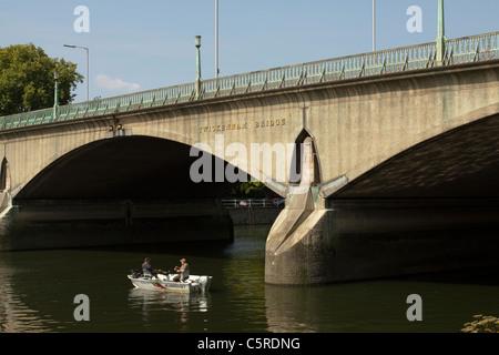 Men fishing from a boat next to Twickenham Bridge, Richmond, Surrey, England, UK - Stock Photo