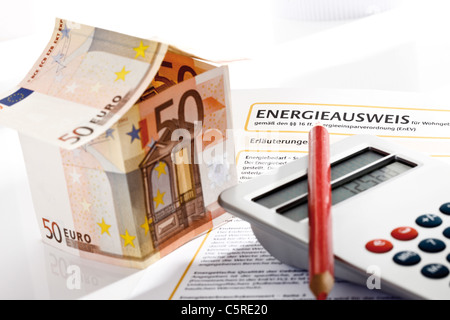 House made from Euro notes, pocket calculator and energy pass, close-up - Stock Photo