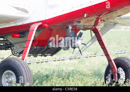 Pump turbine and spray nozzles under the wings of an airplane used in aerial application of agricultural chemicals - Stock Photo
