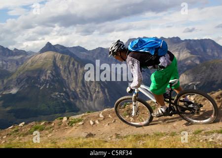Italy, Livigno, View of man riding mountain bike downhill - Stock Photo