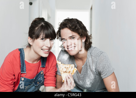 Germany, Cologne, Close up of young couple having lunch break in renovating apartment, smiling, portrait - Stock Photo