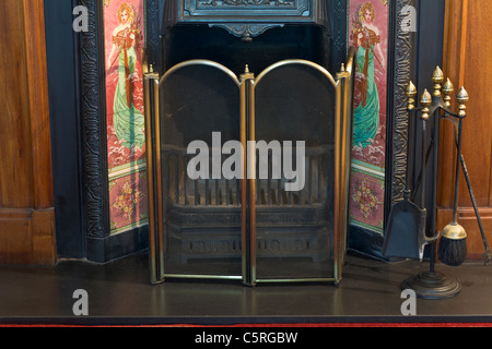 Cast iron open fireplace with fireguard - Stock Photo