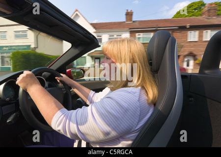 Woman driving a convertible, open top, Mercedes sports car