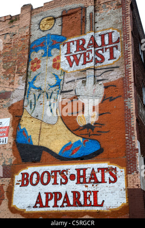 trail west painted wall mural advert for cowboy boots hats and apparel Nashville Tennessee USA - Stock Photo