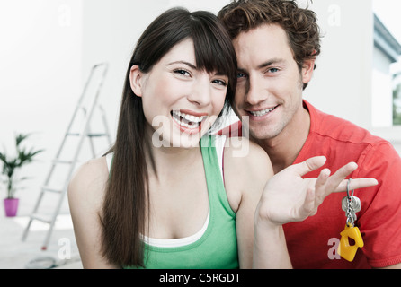 Germany, Cologne, Close up of young couple holding house keys in renovating apartment, smiling - Stock Photo