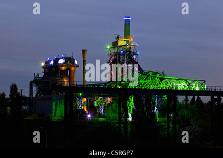 Germany Illuminated blast furnace and smoke stacks of old industrial plant - Stock Photo