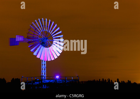 Germany, Nordrhein-Westfalen, Duisburg, Duisburg-Nord Landscape Park, View of illuminated wind mill of industrial - Stock Photo