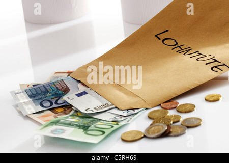 Wage packet, Euro coins and Euro bank notes, close-up - Stock Photo