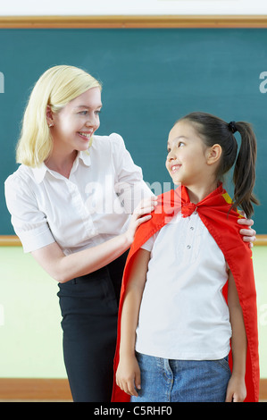 A girl and a teacher smiling to each other - Stock Photo