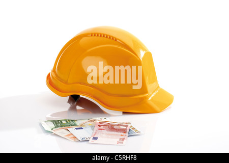 Hardhat and different Euro bank notes in foreground - Stock Photo