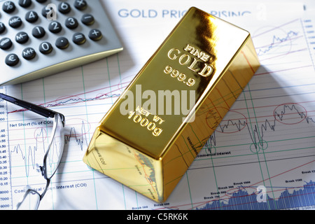 Gold bullion barr on a stocks and shares chart - Stock Photo