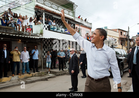 Obama waves to people gathered on the street outside the Cidade de Deus (City of God) favela Community Center in - Stock Photo