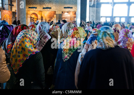 Young muslim women with headscarfs, Ayasofya (Hagia Sophia) cathedral and mosque, Istanbul, Turkey - Stock Photo