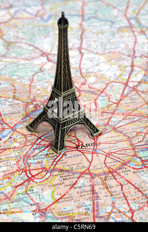 Statue of Eiffel Tower on map of Paris - Stock Photo
