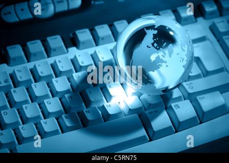Crystal globe on keyboard - Stock Photo