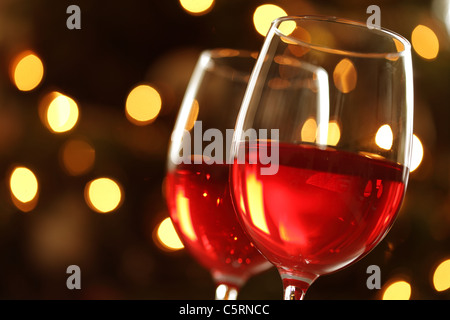 Glass of red wine against defocussed lights - Stock Photo