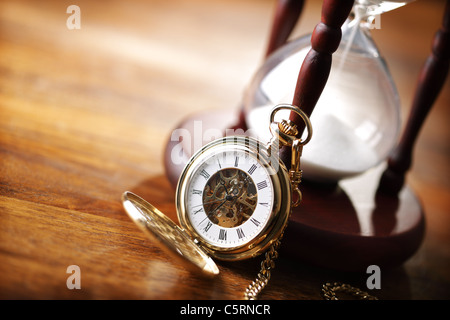 Gold pocket watch and hourglass - Stock Photo
