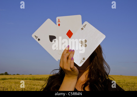 Young woman,holding cards in front of her face. Three of a kind. - Stock Photo