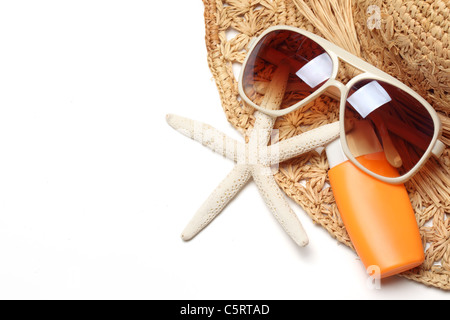 Sunglasses,sunblock and straw hat isolated on white background. - Stock Photo