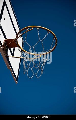 Germany, North Rhine-Westphalia, Düsseldorf, Empty basketball hoop against blue sky - Stock Photo