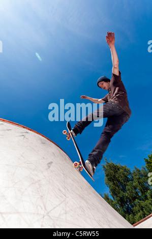 Belgium, Flemalle, Young man skate boarding in skatepark - Stock Photo