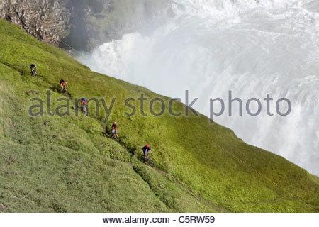 Iceland, Men mountain biking next to waterfall - Stock Photo
