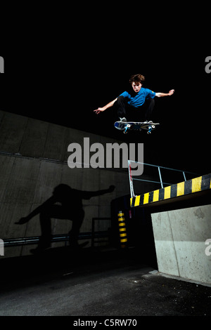 Germany, North Rhine-Westphalia, Duesseldorf, View of young skateboarder performing stunt at night - Stock Photo