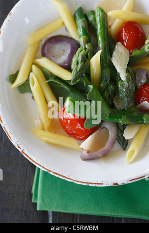 Close up of noodle salad with ruccola, asparagus, parmesan and cherry tomatoes - Stock Photo