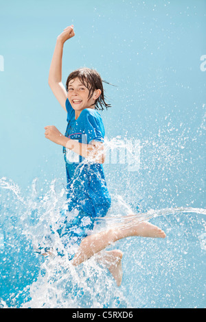 Germany, Boy jumping in splash of water against blue background - Stock Photo