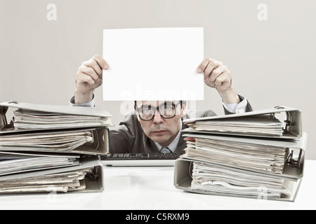 Close up of mature businessman holding blank paper - Stock Photo