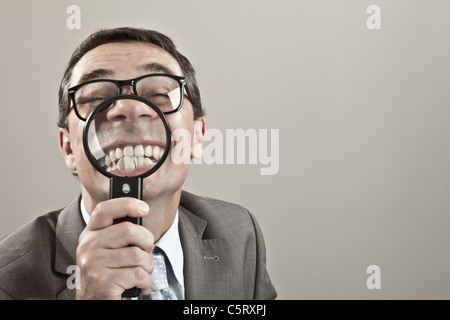 Close up of mature businessman showing teeth through magnifying glass against grey background - Stock Photo
