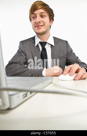 Young businessman working on laptop against white background - Stock Photo