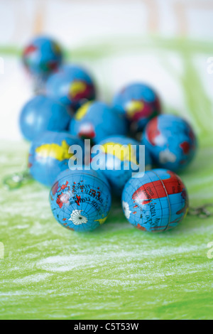Europe, Germany, Close up of earth globes on green background - Stock Photo