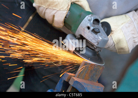 Close up of man sharpening piece of iron with angle grinder - Stock Photo