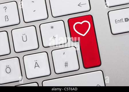 Close up of computer keys with heart symbol on red key - Stock Photo