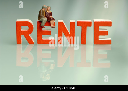 Figurines, Senior couple sitting on top of writing Rente - Stock Photo