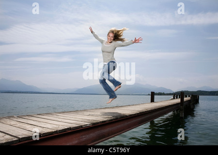 Germany, Chiemsee, Woman jumping on jetty - Stock Photo