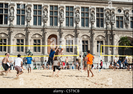 People playing beach volleyball on an artificial field in  front of City Hall during the Paris Plage event, Paris, - Stock Photo