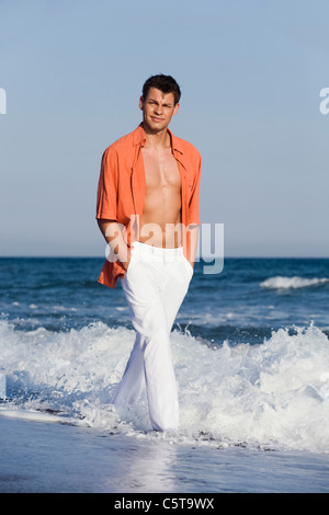 Turkey, Young man walking along beach, hands in pocket, portrait - Stock Photo