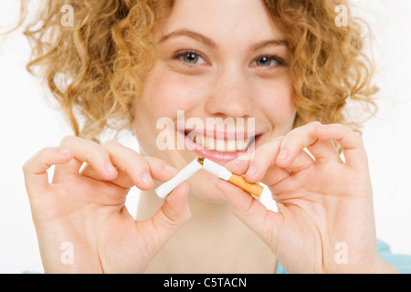 Young Woman breaking cigarette in half, smiling, portrait - Stock Photo