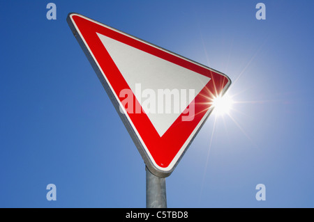 Give way traffic sign against blue sky - Stock Photo